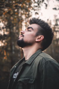 young man with beard takes a deep breath