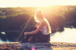 young woman admires sunset in nature
