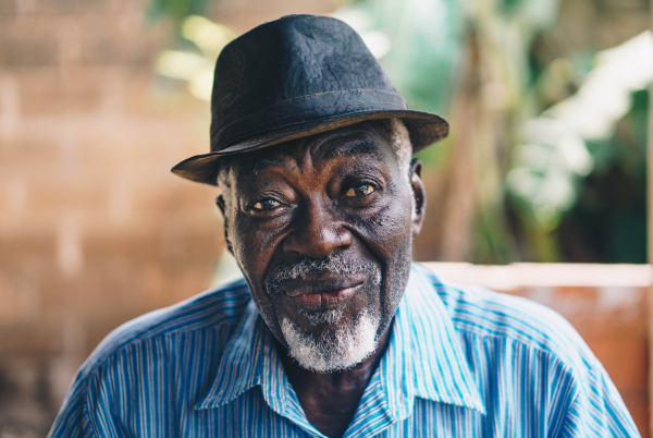 elderly african american man in bowler hat smiling