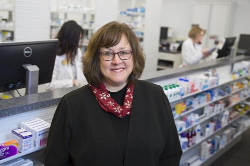 Dr. Karen Hudmon standing in front of a pharmacy window