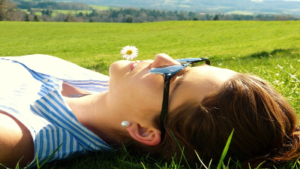 Photo of a person laying in the grass wearing sunglasses