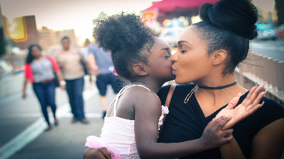 photo of woman kissing a child