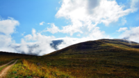 photo of grassy hill with cloudy blue sky