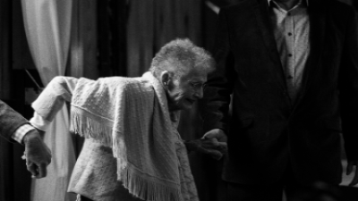elderly woman being assisted as she stands