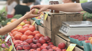 photo of hands passing fruit to one another with a farmers market in the background