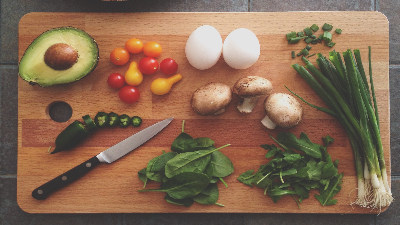 photo of a wooden cutting board with a knife and food