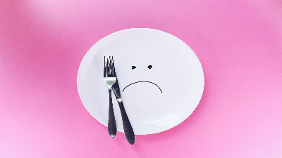 photo of empty plate with sad face and fork and knife