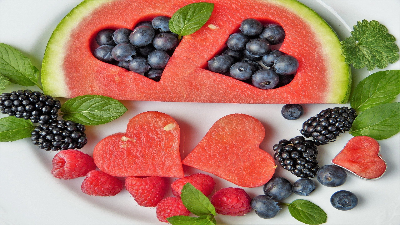 photo of watermelon with hearts cut out and filled with berries