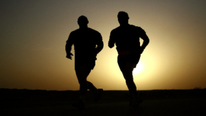 photo of two men running with a sunset behind them