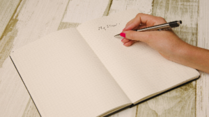 photo of a notebook with the words my plan and a hand with a pen
