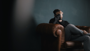 photo of a man sitting on a couch with his hand to his forehead