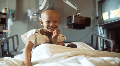 bald child smiles from hospital bed