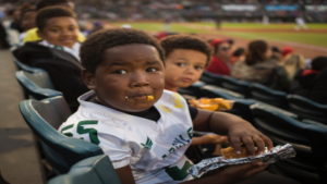 child eating junk food at sports event