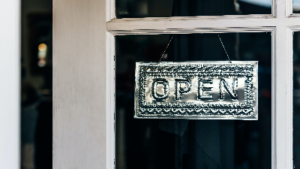 photo of a silver metal embossed open sign hanging in a window