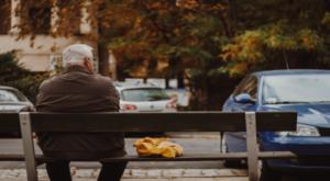 elder gentleman sits on bench looking at street scene